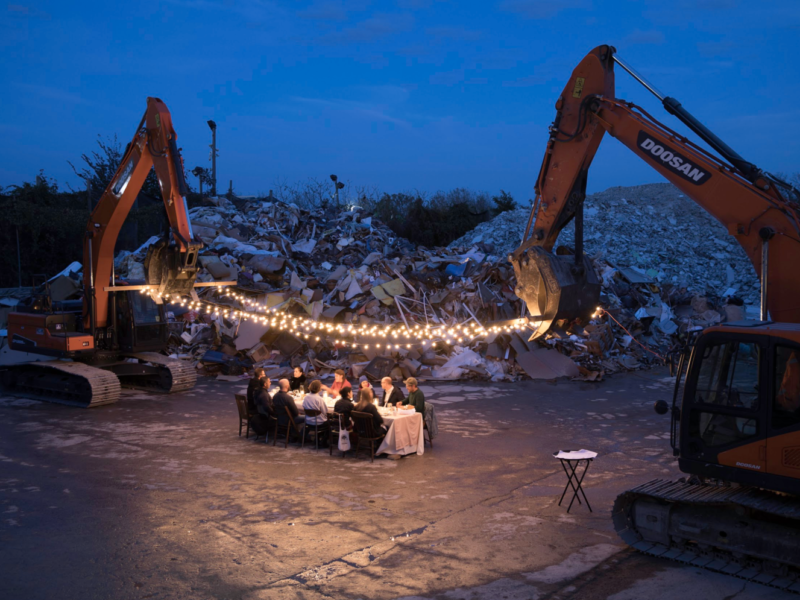 A group of people dining beneath two diggers