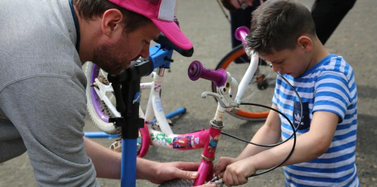Man helping a boy fix a bicycle