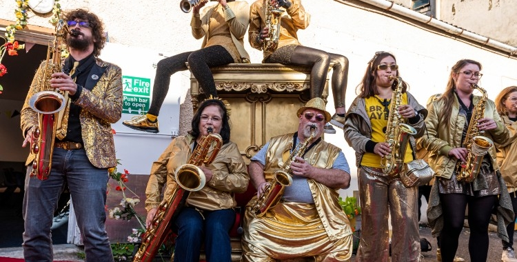 Brass band in gold outfits playing their instruments