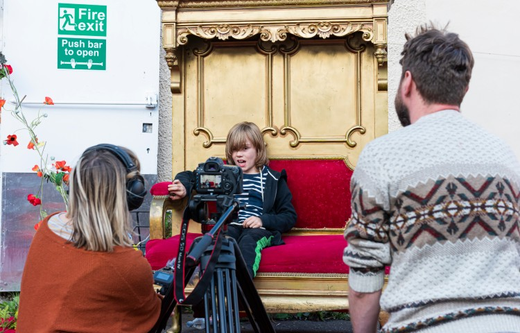 Child sitting on a golden throne being filmed