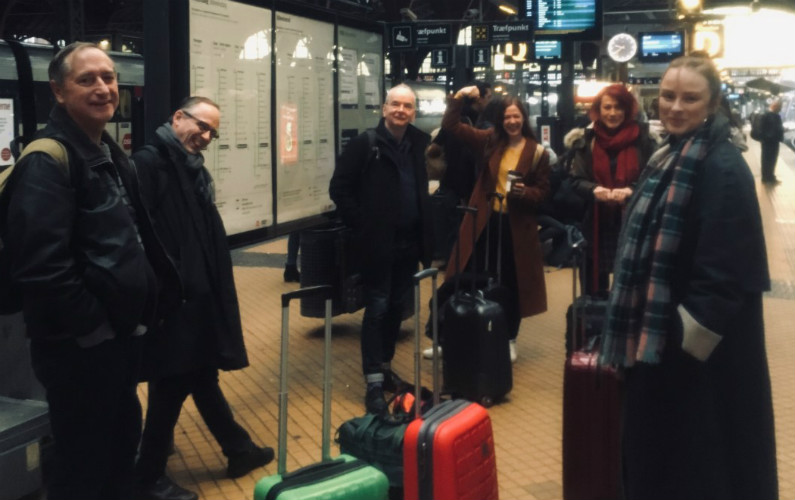 group of people with luggage standing inside a train station