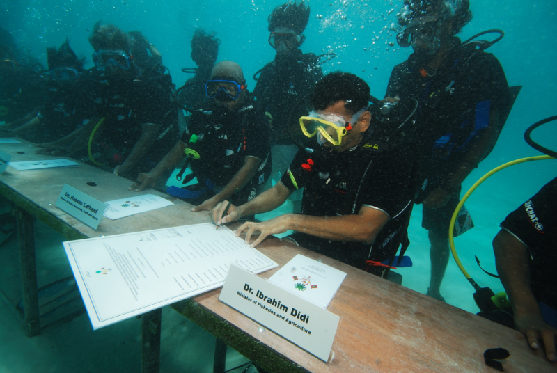 A minister wearing scuba diving gear and signing a decree at a staged underwater cabinet meeting.