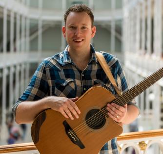 man with a guitar taken in a decorative atrium