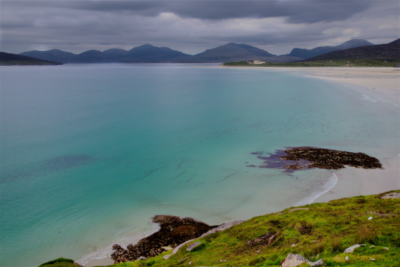 stunning aqua-green sea, white sandy beach with mountains in background; Isle of Lewis