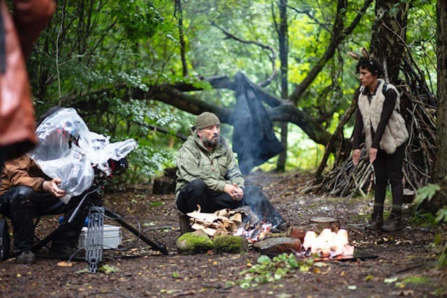 2 people in a forest, around a campfire