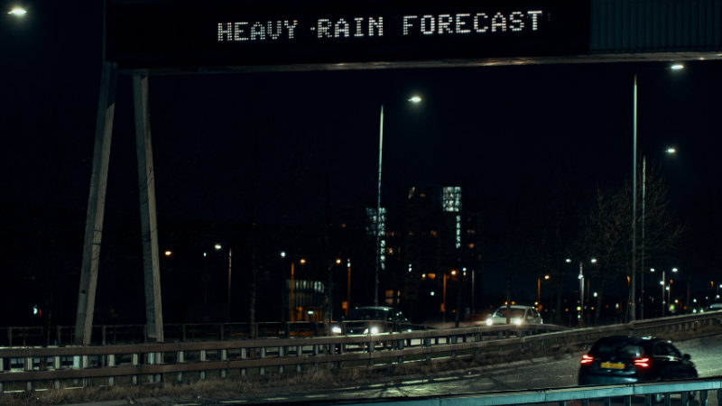 Glasgow night street scene with traffic and a traffic sign reading 'heavy rain forecast' by Ross Sneddon on Unsplash