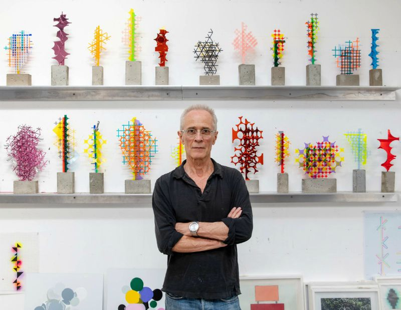 David Batchelor in front of colourful, intricate sculptures