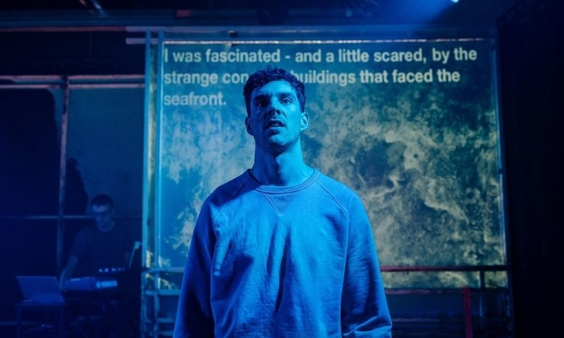 Man standing in front of a board with writing on it, in blue light