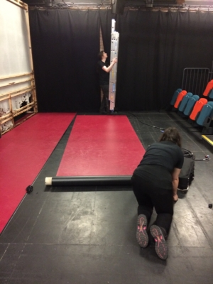 Woman rolling out the dance floor, which is red on top and black underneath
