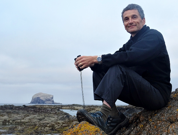 Neil Kitching in outdoor walking clothes sitting on a rock near the sea holding a pair of binoculars, with Bass Rock in the backgrount