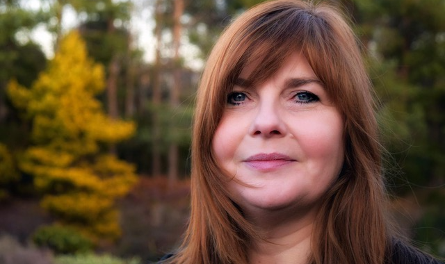 headshot of Emma Nicolson in an outdoor setting. Short depth of field so trees are in soft focus in the background.